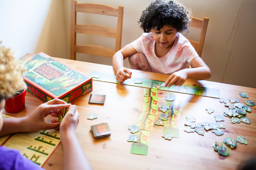 little girl plays alphabet board game