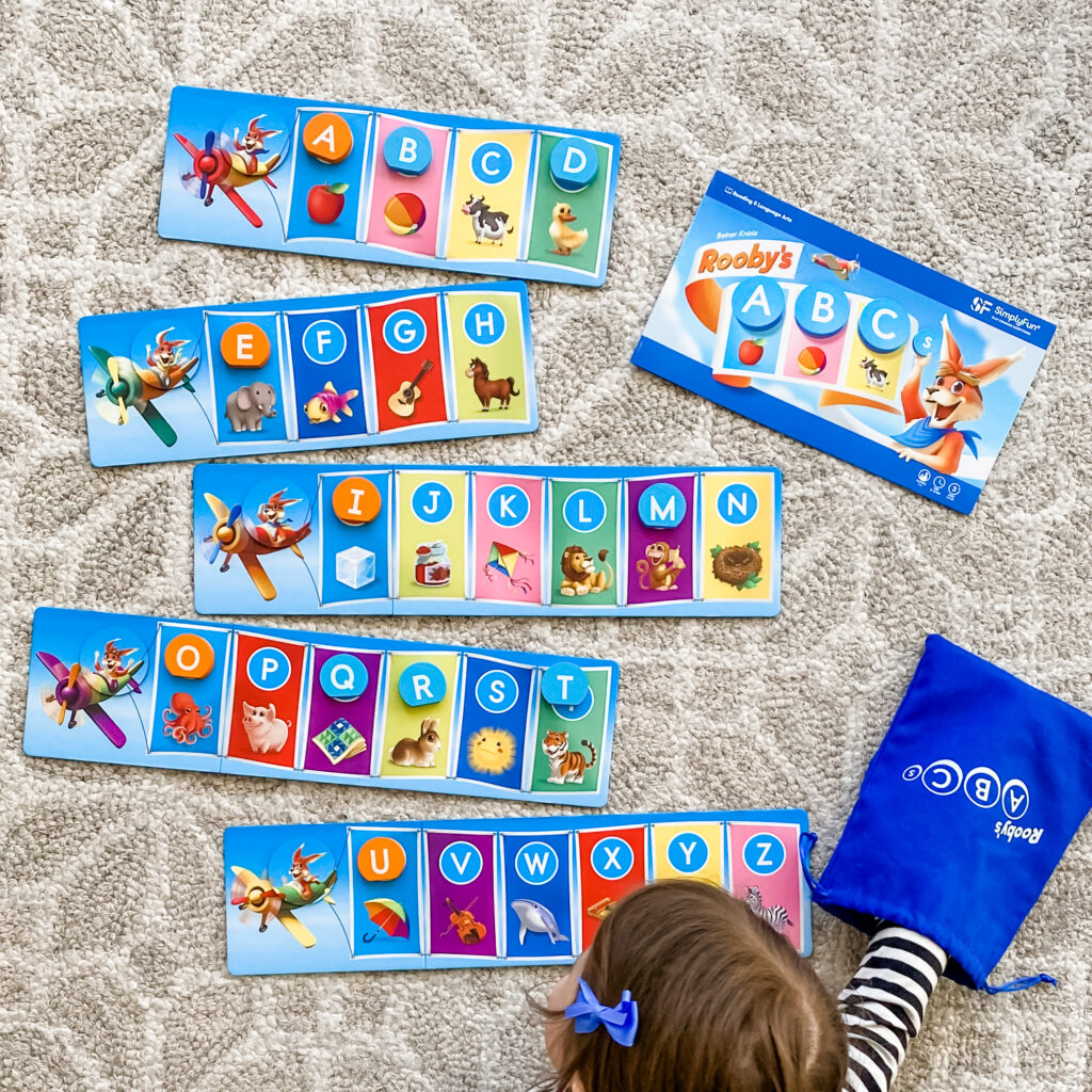 Little girl playing SimplyFun's new early reading game Rooby's ABCs