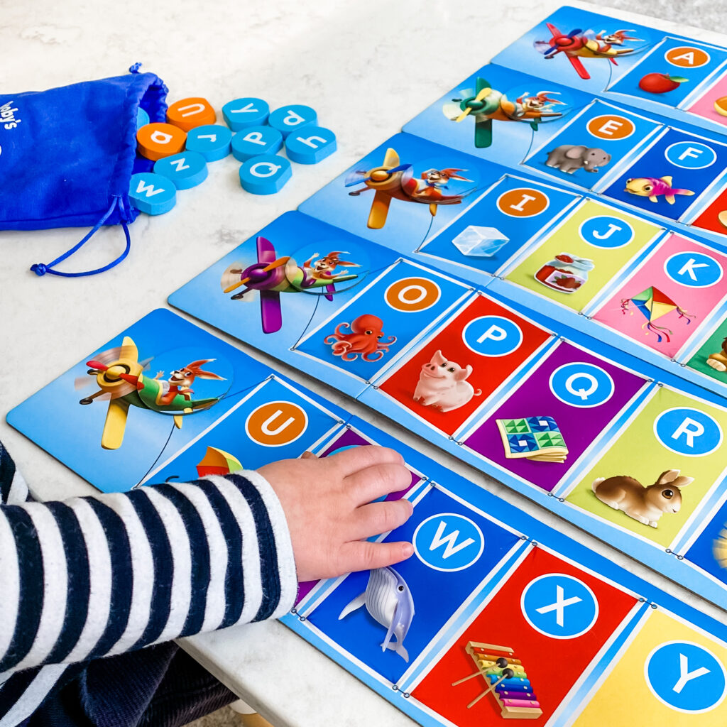 Little girl playing Rooby's ABCs board game