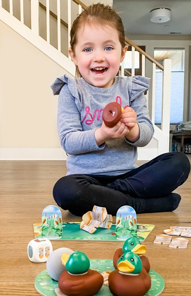 Little girl smiling and holding a Hazel's Helpers duck game piece.